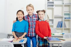 Schoolchildren. Young boy embracing two intercultural classmates in classroom Royalty Free Stock Photography