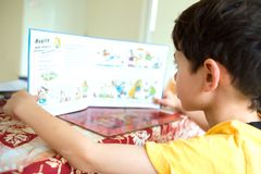 Young boy engross in his storybook. In a home environment Royalty Free Stock Photos