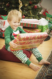 Young Boy Enjoying Christmas Morning Near The Tree Royalty Free Stock Photos