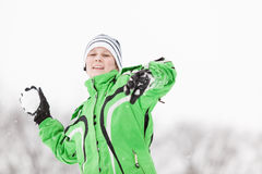 Young boy enjoying the cold winter weather. Smiling happily as he prepares to throw a snowball during a snowball fight, upper body portrait in a winter Stock Photos