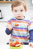 Young Boy Enjoying Healthy Snack Of Fresh Fruit Stock Photos