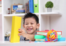 Young boy enjoying his reading book indoor setting. Young boy enjoying his reading a book indoor and setting Royalty Free Stock Image