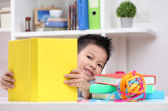 Young boy enjoying his reading book indoor setting. Young boy enjoying his reading book indoor setting Stock Photo
