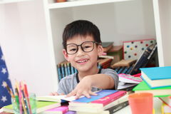 Young boy enjoying his reading book indoor setting. Young boy enjoying his reading a book indoor and setting Royalty Free Stock Images