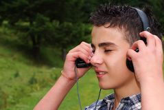 Young boy enjoying music. Nature on the background Stock Image