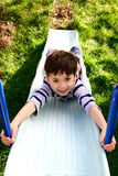 A young boy enjoying the outdoors. On the garden slide Royalty Free Stock Photography
