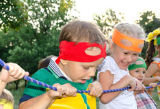 Young boy enjoying a tug of war at a party. Young boy enjoying  tug war party peering over the rope  look amazement  face watched by his laughing young sister Royalty Free Stock Photos