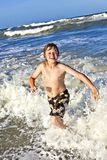 Young boy enjoys the waves of the blue sea Royalty Free Stock Photography