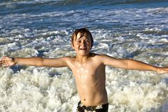 Young boy enjoys the waves of the blue sea Stock Images