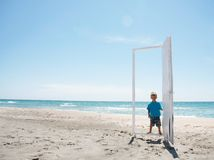 Young boy entering door on beach Stock Images