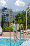 Young boy entering a swimming pool. Carefully climbing down the metal steps inflatable buoyancy jacket hot summer day apartment complex Stock Photos
