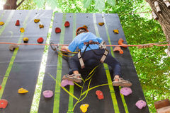 Boy with equipment climber moves up on climbing wall Stock Images