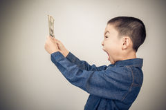 Young boy excite with  american dollar bank note. In his hand Stock Photos