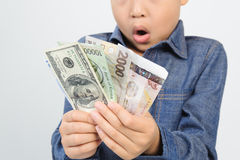 Young boy excite with bank note. Out focus face Young boy excitewith american and korean bank note in his hand Stock Photo