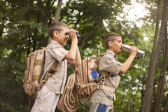 Young boy explores  nature with binoculars on camping trip Stock Image
