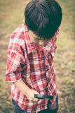 Young boy exploring nature with magnifying glass. Outdoors. Vint Stock Photography