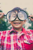 Young boy exploring nature with magnifying glass. Outdoors. Vint Royalty Free Stock Photography