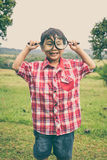 Young boy exploring nature with magnifying glass. Outdoors. Vint Stock Photo