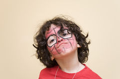 Young Boy Expression. Painting masked boy enjoying the final moments of a birthday party Stock Photos