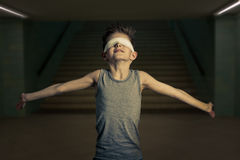 Young Boy with Eyes Covered Opening his Arms Wide. Half Body Shot of a Slim Young Boy with Eyes Covered Opening his Arms Very Wide Against Building Stairways Stock Photos