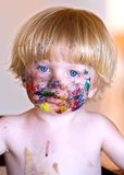 Young boy with face covered in colourful paint. Young boy with blonde hair and face covered in colourful paint royalty free stock photography