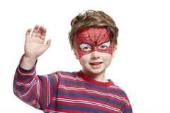 Young boy with face painting spiderman. Smiling on white background royalty free stock photo