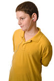 Young boy with ear buds facing camera left. Young boy facing camera left with ear buds in his ears listening to an MP3 player Stock Photos