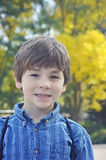 Young Boy Fall. Back to school boy with backpack and fall leaves in the background Royalty Free Stock Images