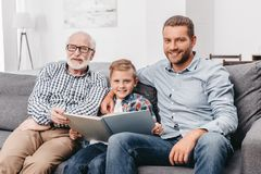 Young boy, father and grandpa sitting on couch in living room and reading a. Book together royalty free stock image
