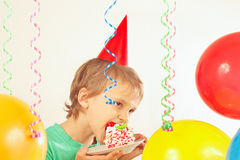 Young boy in festive hat eating birthday cake Stock Images