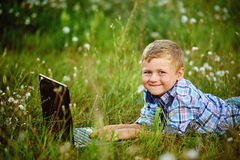 Young boy in field with dandelions with a laptop Stock Photography