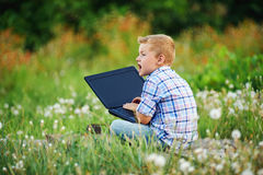 Young boy in field with dandelions with a laptop Stock Photo