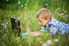 Young boy in field with dandelions with a laptop Stock Photos