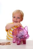 Young boy fills his piggy bank Royalty Free Stock Photos