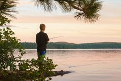 Young boy fishes at a lake at sunset royalty free stock photography