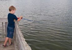 Young Boy Fishing. A photo of a young boy with his fishing pole at a lake Stock Images