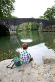 Young boy fishing near old bridge Royalty Free Stock Images