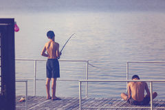 Young boy fishing on a pontoon Royalty Free Stock Image
