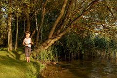 Young boy is fishing in a river Royalty Free Stock Image