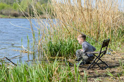Young boy fishing with a rod and reel. On the shores of a calm lake squatting down alongside the water near a bank of reeds Stock Images