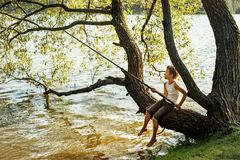 Young boy is fishing while sitting on a tree branch over a river Royalty Free Stock Images