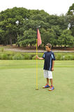 Young boy with flag on golf course. Young boy holding a flag by a hole on a golf course Stock Photo