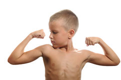 Young boy flexes his muscles. Handsome muscular young man flexing biceps, isolated Royalty Free Stock Photos