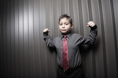 Young boy flexing his muscles Stock Photo