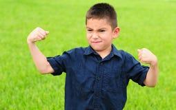 Young boy flexing his muscles stock photos