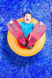 Young boy in flippers playing in a pool Stock Image