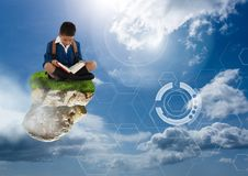 Young boy on floating rock platform  in sky reading book with futuristic interface. Digital composite of Young boy on floating rock platform  in sky reading book Royalty Free Stock Images