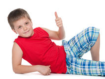 Young boy on the floor holds his thumb up Stock Image