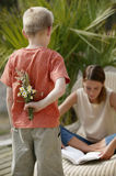Young boy with flowers. Young boy about to surprise his mother with flowers stock image