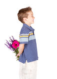 Young boy with flowers behind his back Stock Image